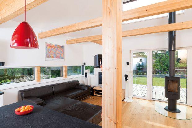 V interiéru dominuje bílá. Barevné řešení zpestřuje tmavá sedačka a deska linky a červená barva doplňků. FOTO MARTIN ZEMAN
