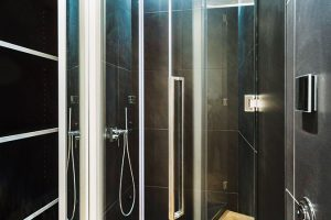 Sprchový kout se nachází vně zasklené kostky, vníž je umístěna vana asamostatně stojící umyvadlo. FOTO TOMÁŠ MALÝ