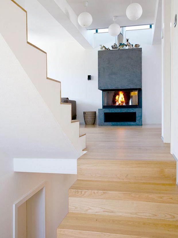 """Na oheň vkrbu otevřeném ze tří stran je vidět zobývacího pokoje izjídelny. """"Rádi sedáváme před krbem, ale ideální křeslo sem ještě hledám,"""" konstatuje architekt amajitel vjedné osobě. Foto ITB Development"""