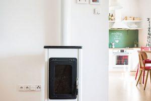Starý komín je ještě funkční apícka se vzimě hojně využívá. Jedním zmála zásahů do dispozice bytu bylo zbourání příčky mezi kuchyní asousedním pokojem tak, aby se denní prostor spojil. Foto Jakub Čaprnka aNora Sapárová