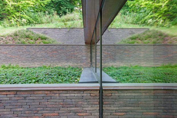 Na severní straně definují jednotlivé úrovně budovy cihlové zdi, korespondující stoupající terén. Velký podíl denního světla vstupuje do podzemního podlaží skrze sloupko-příčkovou fasádu ze systému Schüco ( AWS 75.SI) foto Laurent Brandajs
