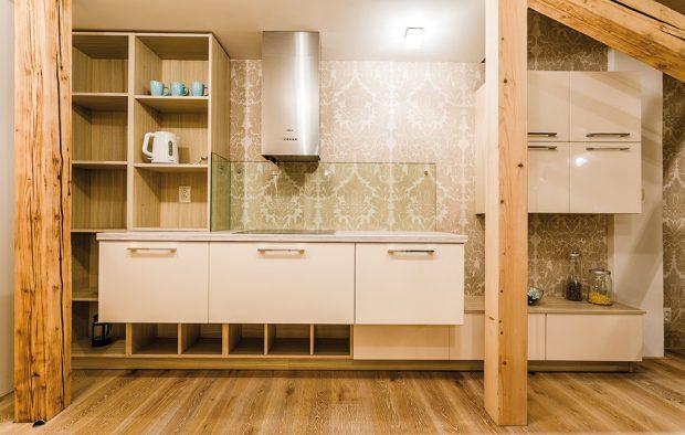 Kuchyně svým vzhledem připomíná nábytkovou sestavu. Nechybějí tu otevřené police, které ji oživují. Nevšedním zpestřením je ivýraznější vzorovaná tapeta tlumených barev. FOTO MARTIN MATULA