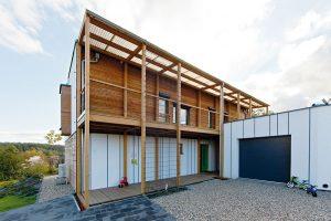 Konstrukce zdřevěných trámů zdobí také severní část domu, kde se nachází ihlavní vchod. Spodní ochoz architekt doplnil rovnoběžným balkonem vprvním patře. FOTO JIŘÍ VANĚK