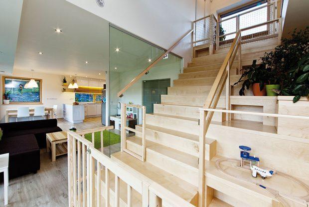 Interiér překvapuje svou integritou. Kuchyňský kout sobývacím pokojem amultifunkčním schodištěm působí jako jednolitý celek. FOTO JIŘÍ VANĚK