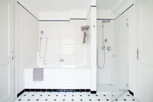 Vprostorné koupelně vhorním patře je kdispozici jak vana, tak sprchový kout svěrnými replikami dobových sprchových hlavic. Jednoduchý obklad abílo-černá podlaha dotvářejí elegantní ačistý vzhled místnosti. FOTO ROBERT ŽAKOVIČ