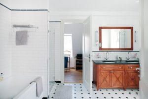 Koupelna je průchozí ze dvou stran. Z ložnice majitelů je praktický přístup přes šatnu. V jednoduché místnosti se krásně vyjímají i dřevěné umyvadlové skříňky a zrcadlo s dřevěným rámem. FOTO ROBERT ŽAKOVIČ