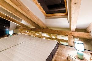 Domácí se rozhodli nepoužívat vložnici ani noční stolky. Příruční lampy se nacházejí volně na podlaze. Díky tomuto řešení tak plně vyniká použité dřevo avýhled na oblohu. FOTO MARTIN MATULA