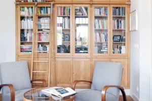 Odpočinkový kout pracovny skřesílky ana míru vyrobenou dřevěnou knihovnou přímo vybízí kposezení sknížkou. FOTO ROBERT ŽAKOVIČ