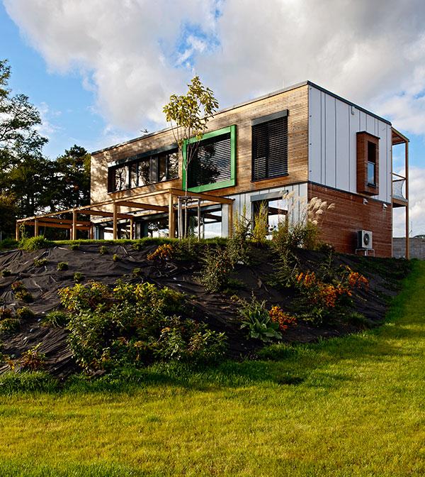 Propojenost domu spřírodou podtrhli realizátoři výběrem dřeva jako obnovitelného stavebního materiálu nebo aplikací zeleného detailu na jižní předstěnu domu. Za tímto okenním rámem se nachází speciální vanová místnost. FOTO JIŘÍ VANĚK