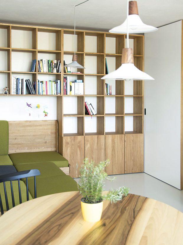 Oživujícím prvkem denní části je zelené čalounění sedačky. Její korpus je vyroben z téhož dubového dřeva jako knihovna i část kuchyňské linky, což prostor sjednocuje. FOTO SCHWESTERN