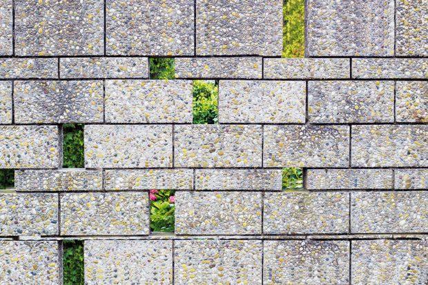 Trendové betonové zdi představují poměrně rychlou afinančně přijatelnou možnost, jak ohraničit větší zahradu. Vyšší betonové bloky však mohou působit rušivě. Aby vypadaly zajímavěji, můžete vnich vytvořit malé průhledy. FOTO ISIFA/SHUTTERSTOCK