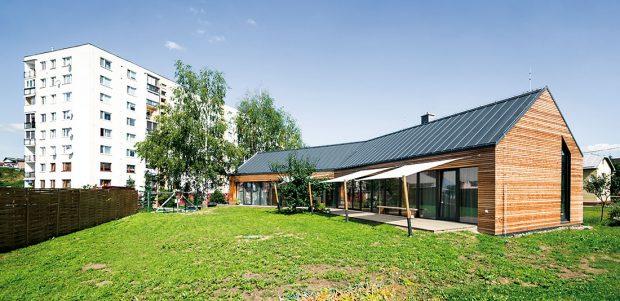 Vdobré formě. Díky tvaru připomínajícímu tradiční stodolu aumístění na pozemku, které respektuje sousední rodinné domy, se novostavba harmonicky začlenila do okolního prostředí. Navíc tak může dům maximálně využívat solární zisky adomácí slunnou část zahrady. FOTO: ERIKA BÁNYAYOVÁ AMARTIN BOLEŠ