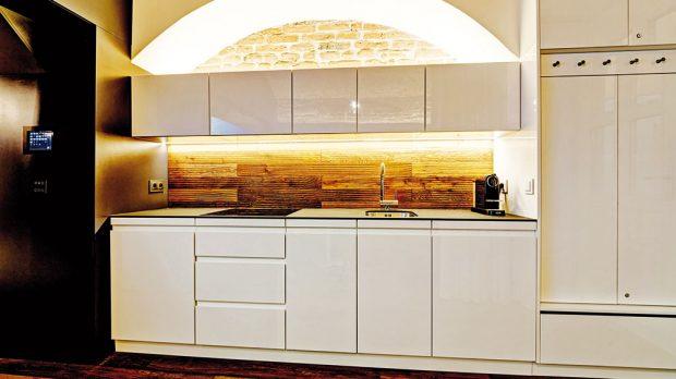 Dřevo se dá do kuchyně aplikovat vrůzných podobách. Třeba jako obložení za kuchyňskou linku, které bude korespondovat sdřevěnou podlahou. FOTO KAMIL SALIBA