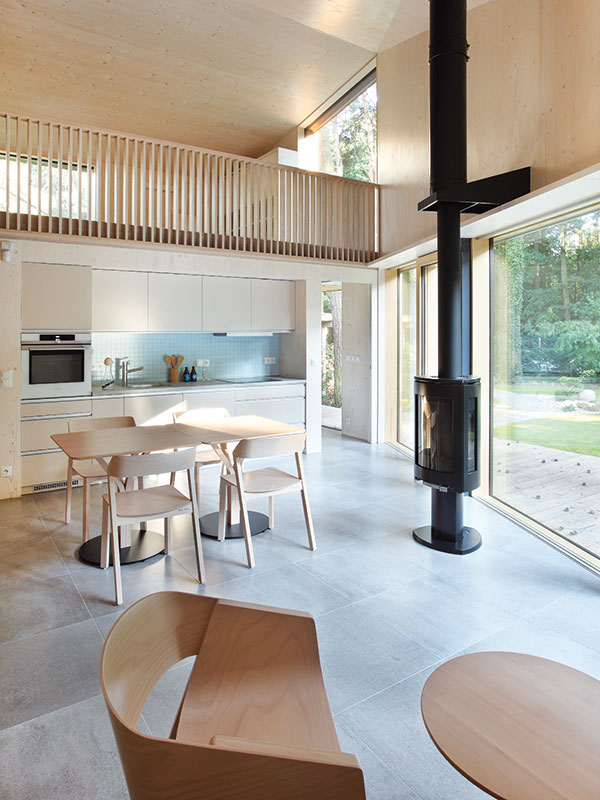 Krbová kamna, která se starají o vytápění celého objektu, jsou umístěna téměř v centru dispozice obývacího pokoje. Působí jako zajímavý kontrast k celodřevěnému interiéru. FOTO PRODESI