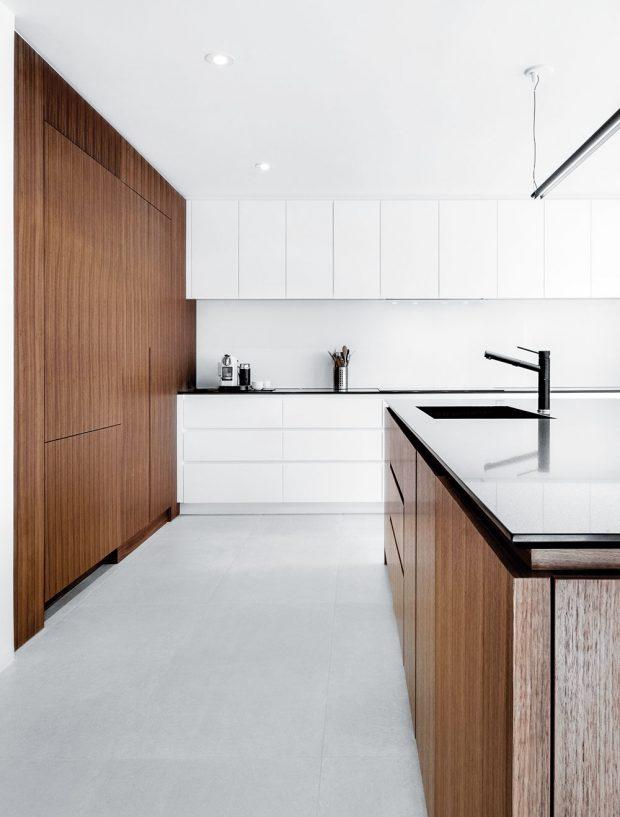 Kombinace bílých skříněk stmavým dřevem nechává vyniknout minimalismus kuchyně. Dalšími barvami by se tato jednoduchost vytratila. Foto v2com