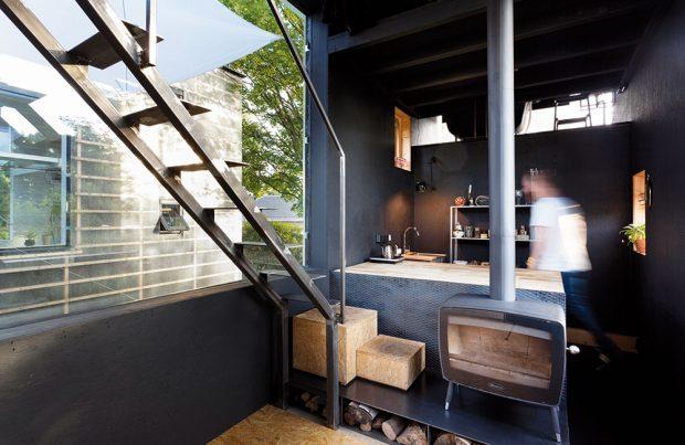 Černě vymalovaný obytný dům koresponduje se svým bílým protějškem, ale tlumené tmavé barvy působí vkombinaci skrbovými kamínky tepleji. FOTO Alexandra Timpau (www.alextimpau.com)