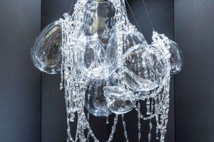 """Závěsný lustr Memento mori od Maxima Velčovského svým tvarem kostí alebek vtištěných do skleněné formy odkazuje na kostnici vSedlci uKutné Hory. Velké části jsou ručně foukané amalé kosti, tvořící řetězy, mají parafrázovat klasické, """"nesmrtelné"""" lustry. Foto Lasvit"""