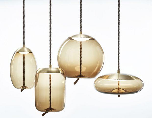Kolekce majestátních závěsných svítidel KNOT od návrháře Chiaramonte Marina (Chiaramonte Marin ) konfrontuje dva odlišné materiály adva odlišné principy – měkkost oblých křivek průzračného foukaného skla atvrdost vypnutého režného lana. Plné zaoblené tvary protínají robustní lano, které zdánlivě deformuje skleněné dno avytváří tak plastický, elastický efekt. Uzel, do něhož lano ústí, je charakteristickým výtvarným prvkem celého konceptu. Světelný LED zdroj je shora elegantně překryt kovovým výliskem azároveň chráněn zespodu ručně foukaným opálovým difusorem. Svítidla Knot se hodí do soukromých iveřejných interiérů. Kolekce se skládá ze čtyř závěsných svítidel aněkolika barevných variací. Foto Brokis