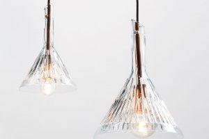 Svítidlo Ribbed Cone Lights, tvořené měděnou konstrukcí, skleněným tělem atextilním kabelem, ovšem vdalší originální podobě, nabízí Kavalierglass. Svítidlo vysoké 245 mm je vyrobeno zčirého laboratorního skla ajeho inspirace je více než zřejmá. Foto Kavalierglass, Michal Seba