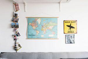 Poměrně neutrálnímu interiéru, vněmž dominují hlavně odstíny šedé adřevo, dodávají svěžest doplňky adekorace. Sedačku oživuje změť polštářů, prostor nad ní mapa světa afotografie zrůzných událostí avýletů po světě. FOTO NORA AJAKUB ČAPRNKOVI