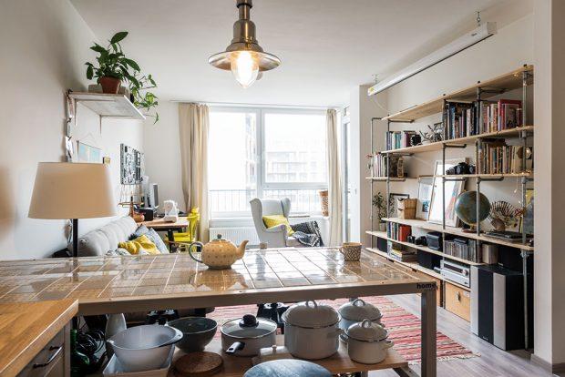Pult na kolečkách, který slouží jako jídelní stůl, se vminulosti používal na vystavení bytových doplňků. Strohou dřevěnou desku nahradili vzorovaným obkladem. FOTO NORA AJAKUB ČAPRNKOVI