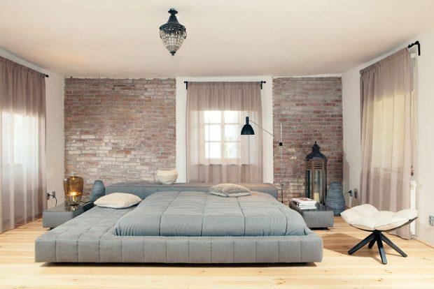 Dominantou spodní ložnice je ikonická postel Squaring Bonaldo. Elegantní místnost doplňuje tlumená barva závěsů, která ladí scihlovou zdí ipolštáři. foto Robert Žákovič