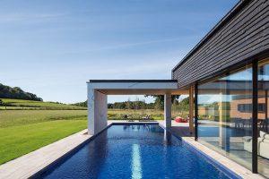 Dlouhý bazén kopíruje jednu stěnu domu. Prosklené okenní tabule se dají posouvat a voda tak téměř prostupuje interiér. FOTO DIRK LINDNER PRO KETTAL