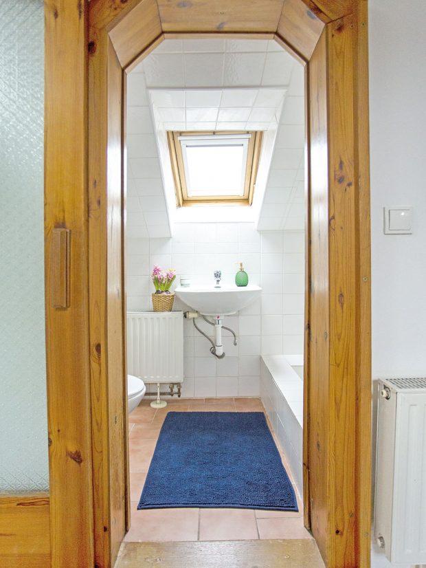 Za dřevěným portálem se ukrývá malá koupelna se sprchovým koutem. foto www.browneyedcouple.com