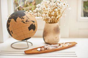 Spousta drobností a suvenýrů zdobí celý byt. Do korkového globusu si Reinout špendlíčky označuje, která místa na světě už navštívil. FOTO Westwing Home & Living