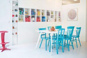 Každý pes, jiná ves. Židličky u jídelního stolu jsou každá jiného tvaru, majitel je ale sjednotil alespoň barevně a na nátěr použil výrazný tyrkysový odstín. FOTO Westwing Home & Living