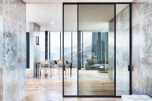 Posuvné dveře Strong jsou tvořeny stejným hliníkovým profilem jako dveře Master. Tentokrát je ale nosnou částí střed tohoto profilu, do kterého je zasazena tabule skla. Jedná se oelegantní celoskleněný typ dveří, který přiznává nosnou konstrukci, adveře se při zavírání skládají přes sebe. Foto J.A.P.