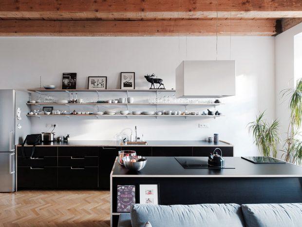 Prostor kuchyně je určen dlouhou linkou aostrůvkem, který zároveň tvoří hranici obývacího pokoje avymezuje místo pro gauč. Tmavě šedá se drží při zemi, bílé umožnili rozlet do výšky. Foto Peter Jurkovič