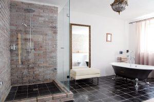 Spodní koupelnu zdobí krásná vana snožičkami izrcadlo se starobylým rámem. Dochovanými prvky jsou tmavá čedičová dlažba acihlový sprchový kout. foto Robert Žákovič
