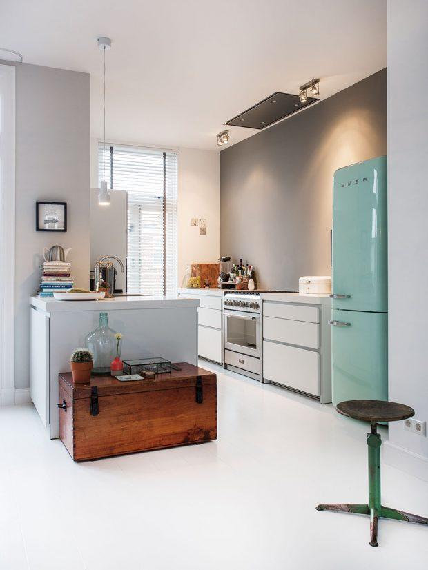 Kombinace světle modré retro lednice Smeg adřevěné truhly přesně vystihuje Odettinu zálibu vrůzných stylech. Foto Femque Schook pro Westwing Home and Living