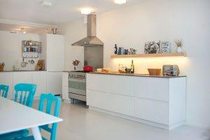 K jednoduché bílé kuchyňské lince se jako doplněk výborně hodí křiklavě barevné židle. FOTO Westwing Home & Living