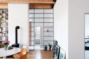 Rozdělení prostoru na denní anoční zónu vyřešil architekt policemi – tento originální prvek se stal poznávacím znamením bytu vTrnavě. Foto Peter Jurkovič
