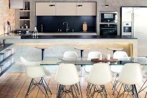 Vatypické kuchyni jsou spotřebiče vsazeny přímo do betonové stěny. Zkuchyňského ostrůvku potom vystupují do jídelní části kamenné police, rovněž vyrobené zbetonové stěrky ažuly. foto Robert Žákovič