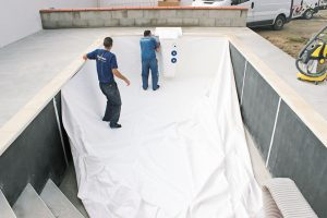 Obrubní dlažba je položena. Následuje osazení lineru, vnitřní výstelky z PVC, svařeného ve výrobním závodě ve Francii přesně na váš bazén.