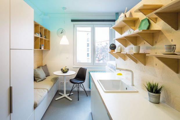 Architekti maximálně využili prostor na stěnách anad kuchyňskou linku umístili odkládací poličky, nad sezením vkuchyni zase větší police. FOTO MARIE KUKULOVÁ