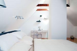 Světlou, bílou ložnici pro hosty, která se nachází vprvním patře, zdobí mimo jiné elegantní průhledná židle. foto Robert Žákovič