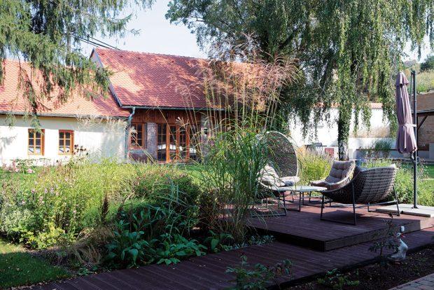 Uprostřed zahrady s bujně rostoucí zelení vzniklo odpočinkové místo s pohodlnými křesly. foto Robert Žákovič