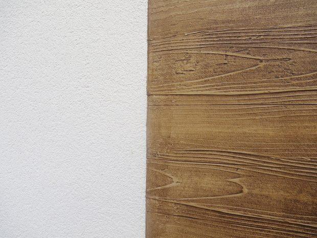 Povrchová úprava Baumit Nanopor Top (minerální pastovitá tenkovrstvá omítka škrábané struktury sfotokatalytickým efektem, který zvyšuje ochranu fasády před biologickým znečištěním) vkombinaci sBaumit Creative Top (jednosložková silikonová dekorativní omítka pastovité konzistence, vhodná zejména ke kreativnímu ztvárnění fasád) – fládrování. FOTO BAUMIT
