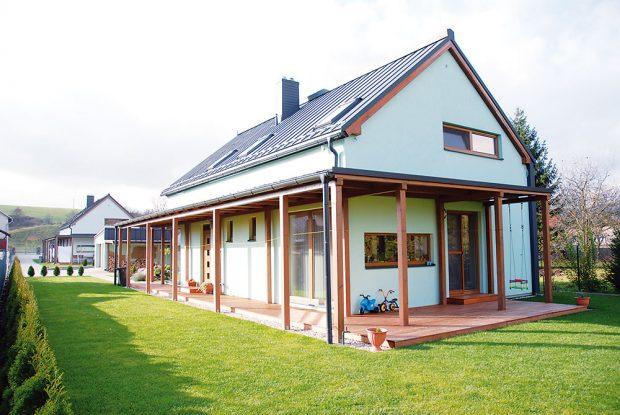 Krytá terasa lemující přízemí je funkční atvarovou transformací tradiční verandy adotváří architekturu domu. Vlétě stíní zasklené plochy azabraňuje tak přehřívání interiéru. (pohled ze zadní části pozemku směrem kpřístupové cestě). FOTO TREEA