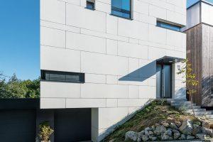 Hladký bílý obklad zvláknocementových desek efektně kontrastuje sokolím aspolečně sgeometrickou hrou okenních otvorů dodává domu moderní ačistý, rozhodně však ne nudný vzhled. (Pásové okno vlevo dole vede do kuchyně, vpravo nahoře do koupelny, prostřední osvětluje prostor schodiště.) FOTO BORIS MELUŠ