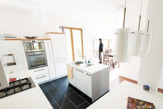 Kuchyň sjídelnou zabírá celou šířku přízemí na východním konci domu. Logicky členěný prostor zařídili praktickou jednoduchou bílou linkou, hranici mezi kuchyní ajídelnou naznačuje rozdílná podlaha akuchyňský ostrov. FOTO TREEA