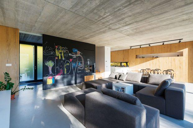 Dubová dýha charakterizuje další ze stěn avnáší do interiéru příjemné tóny dřeva. Hladká dvířka skříní vobývacím pokoji navazují na kuchyňskou linku aspolu vytvářejí homogenní nábytkový blok. FOTO BORIS MELUŠ