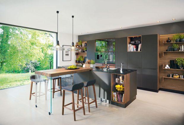 Tmavé přírodní dřevo skříněk působí vkombinaci sčerným matným sklem elegantně. Kuchyni od TEAM 7 si můžete poskládat přímo podle vašich představ.