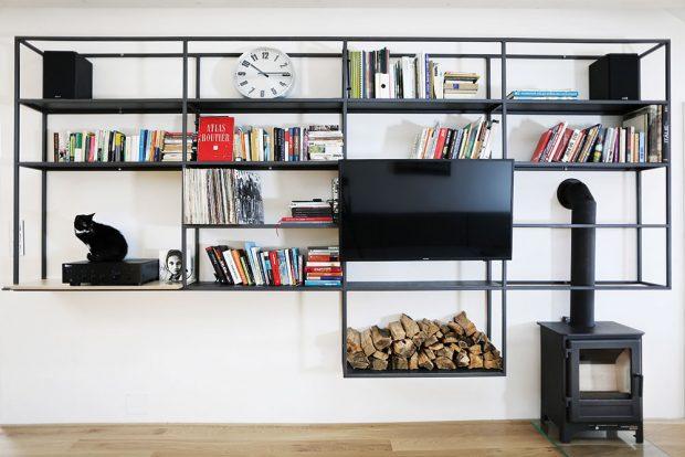 Ocelová mřížka unese knihy, gramofon, palivové dříví, přizpůsobuje se kouřovodu amírní vizuální konflikt krbových kamen stelevizí. Foto TRAGA