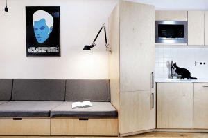 Interiér je na několika místech ozvláštněn výraznějším prvkem. Světlé odstíny březového dřeva sedačky například doplňuje extravagantní plakát. Foto TRAGA