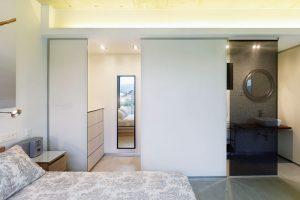 Ke světlé ložnici za strany navazuje šatní aumyvadlová část se zrcadly, která je oddělená roletou. Foto HECTOR SANTOS DIEZ